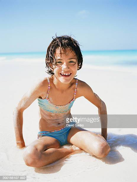 Girl (8-10) on beach, smiling, portrait