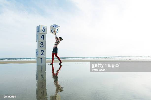 Girl on beach stacking numbered boxes