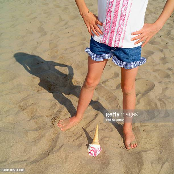Girl (7-9) on beach, upturned ice cream in sand at feet, low section