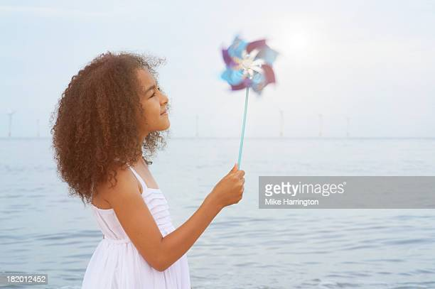 Girl on beach using toy windmill