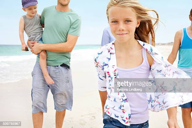 Girl on beach walking to camera with family behind
