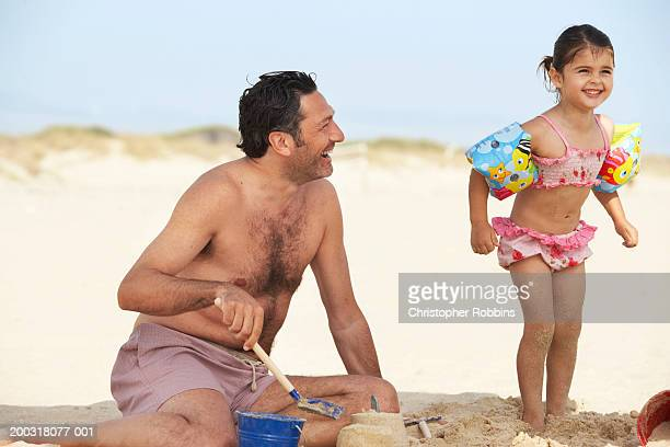 girl (2-4) on beach wearing arm bands, standing next to father - female hairy chest stock pictures, royalty-free photos & images