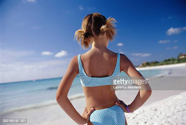 Girl (8-10) on beach wearing bikini, hands on hips, rear view