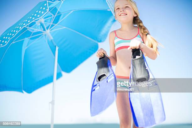Girl on beach with flippers at sunshade