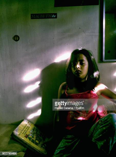 Girl On Bed Against Wall At Home