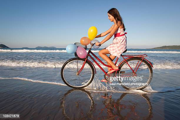 Girl on bicycle at beach