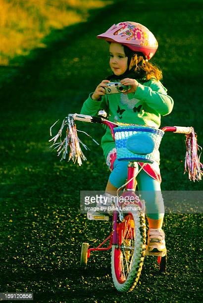 Girl on bicycle holding a camera