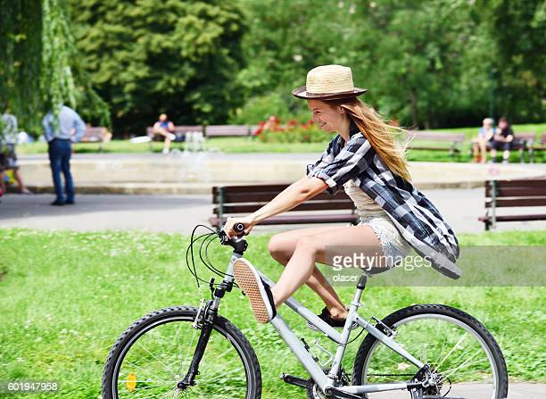 Girl on bicycle in summer city park, copy space