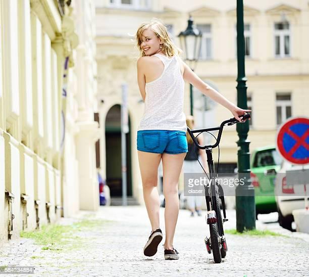 Girl on bicycle 'kick bike' in summer city