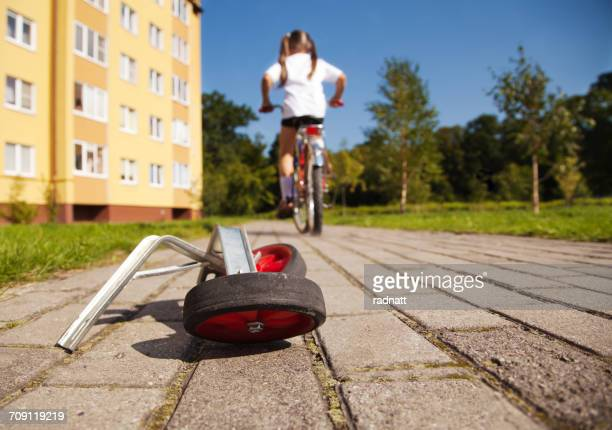 Girl on bicycle leaving her training wheels behind