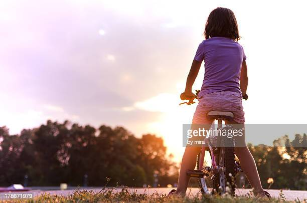girl on bike at purple sunset - alleen één meisje stockfoto's en -beelden