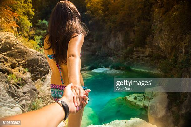 Girl on bikini leading the way in the beautiful natural pools in a Pyrenees river, taking hand of boyfriend that takes pictures from personal perspective in a summer travel. Follow me.