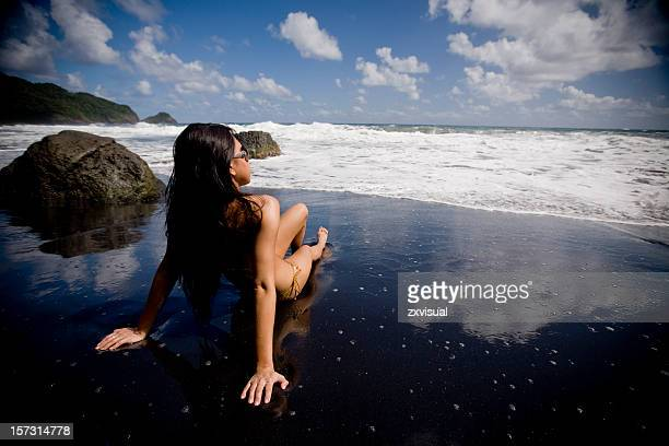 girl on black sands beach in dominica - volcanic terrain stock photos and pictures