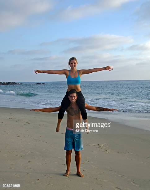 Girl on boyfriend's shoulders at the beach