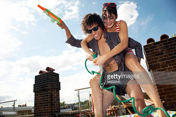 Girl on boy's back having a water fight