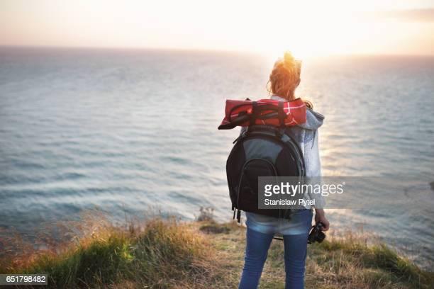 Girl on cliff near ocean at sunset