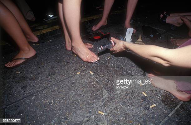 Girl on club dancefloor has her feet cooled by a friend pouring Smirnoff Ice over them Shoreditch London UK 2000s