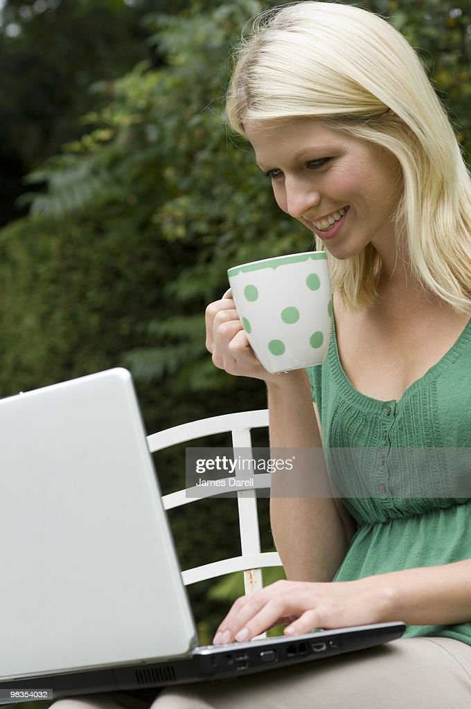 girl on computer with mug : Stock Photo