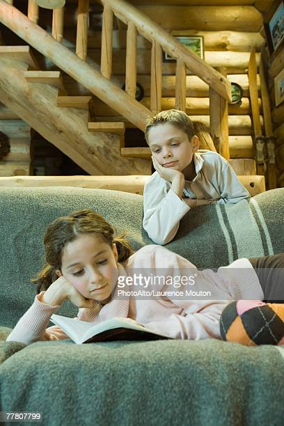 Girl on couch reading book, boy looking over shoulder