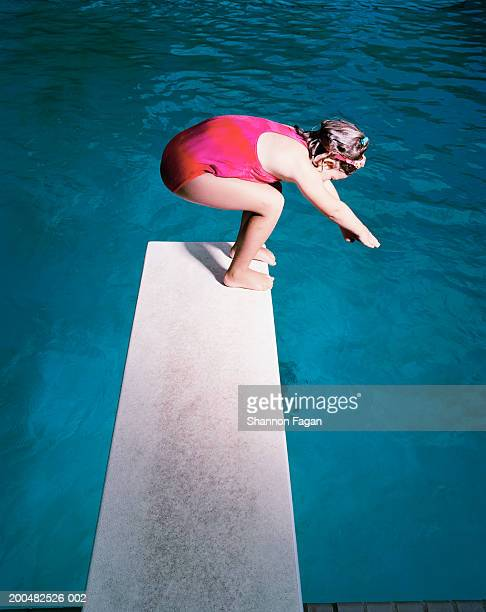 girl (6-7) on diving board at swimming pool - 室内プール ストックフォトと画像