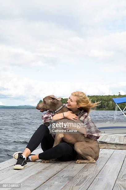 girl on dock with weimaraner dog