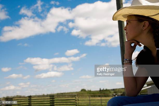 Girl on farm wearing cowboy hat