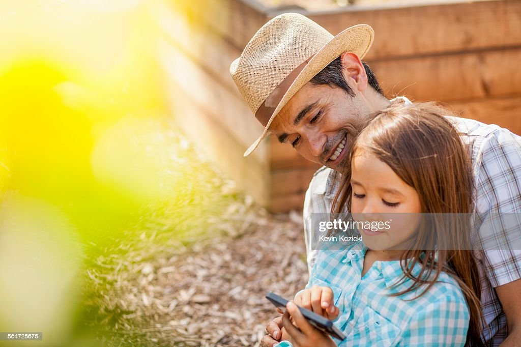 Girl on fathers lap using smartphone in community garden : Stock Photo