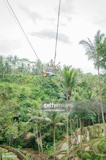 Girl on giant swing in Bali flying over jungle, Indonesia