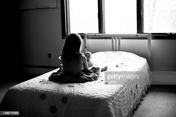 Girl on her bed with baby doll