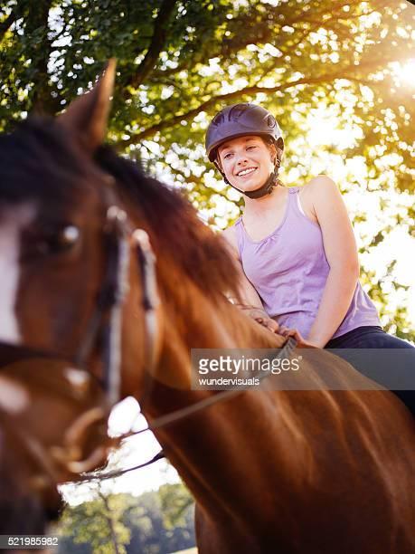 Mädchen auf ihrem Pferd mit goldenen Sonne durch die Blätter Flair
