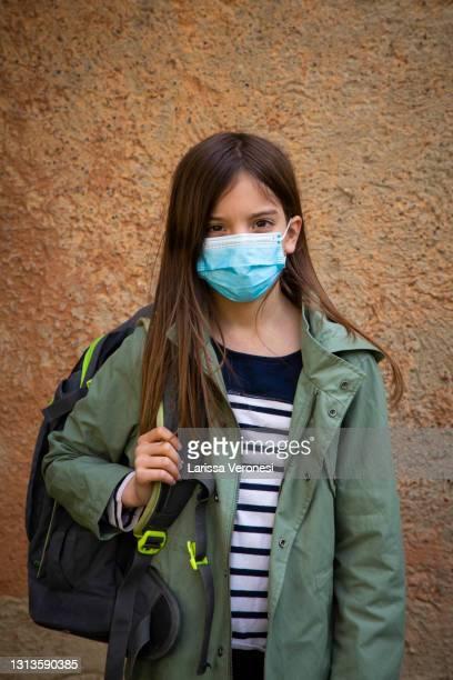 girl on her way to school with medical mask - larissa veronesi stock-fotos und bilder