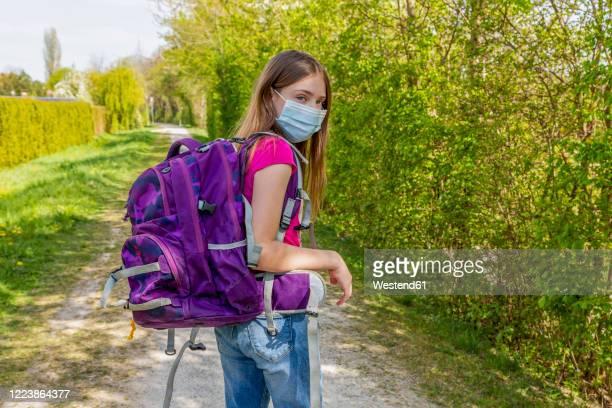 girl on her way to school with protective mask - schulkind nur mädchen stock-fotos und bilder