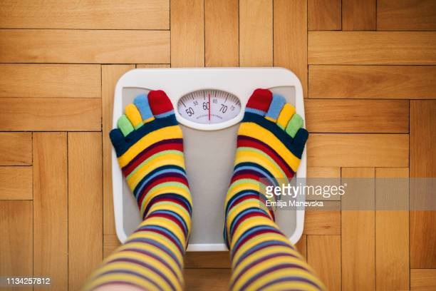 girl on home weight scales - mass unit of measurement stock pictures, royalty-free photos & images