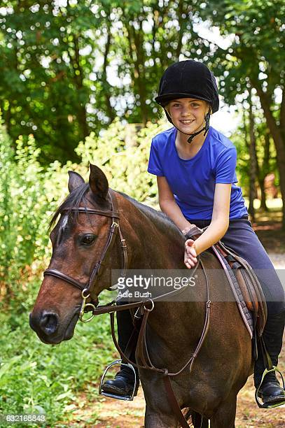 Girl on horse wearing riding hat looking at camera smiling