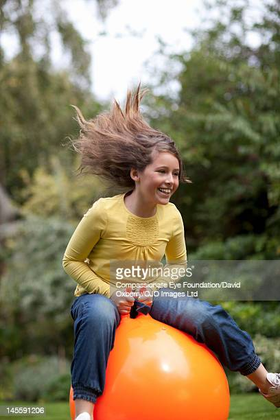 girl (10-11) on inflatable hopper in garden - hoppity horse stock photos and pictures