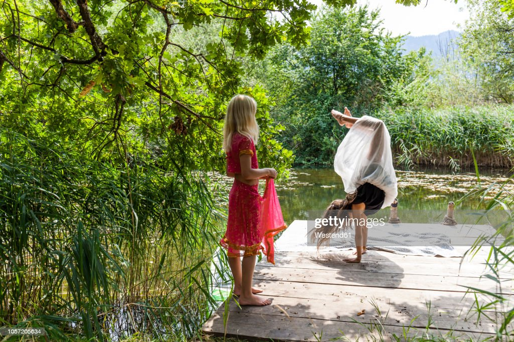 Girl on jetty at a pond watching friend doing a handstand : Stock Photo