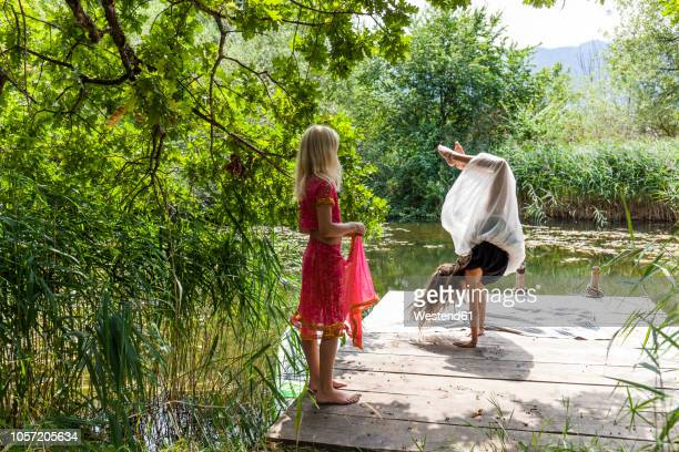 girl on jetty at a pond watching friend doing a handstand - girl in dress doing handstand stock photos and pictures