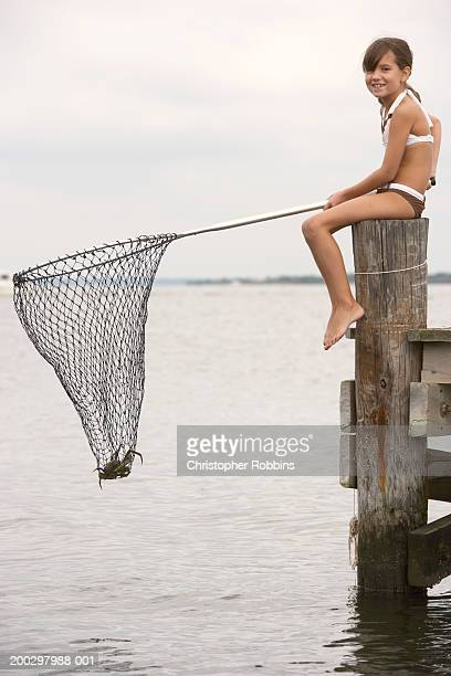 Girl (8-10) on jetty holding fishing net with crab in it, portrait
