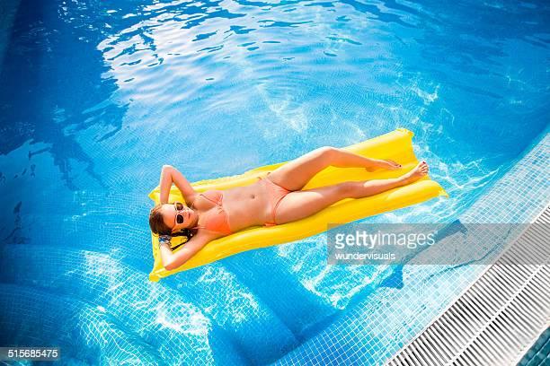 Mädchen auf Lilo im Swimmingpool