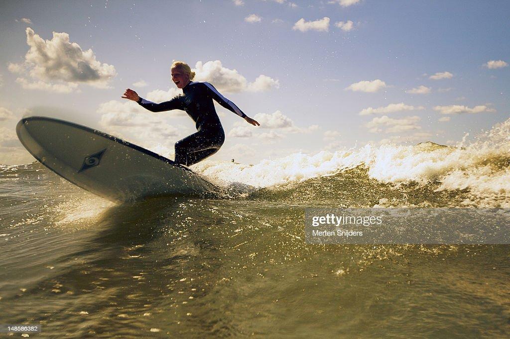 Girl on longboard surfboard on wave. : Stockfoto