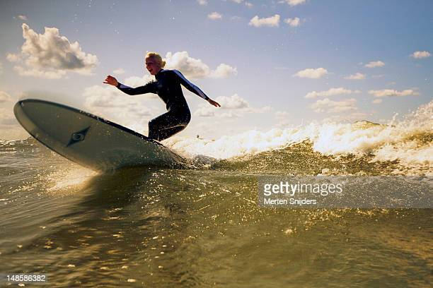 girl on longboard surfboard on wave. - merten snijders stock pictures, royalty-free photos & images