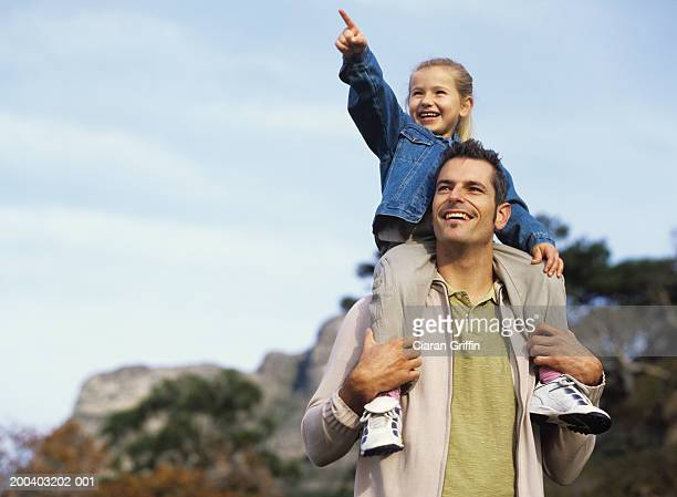 Girl (4-6) on man's shoulders, pointing, low angle