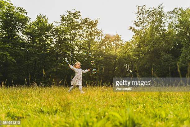 Girl on meadow surrounded by soap bubbles