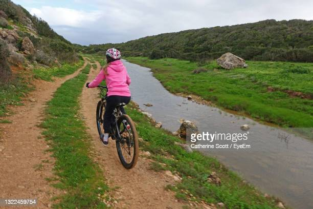 girl on mountain bike cycling along a dirt track next to a river - sagres stock pictures, royalty-free photos & images