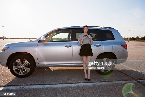 Girl on phone by car