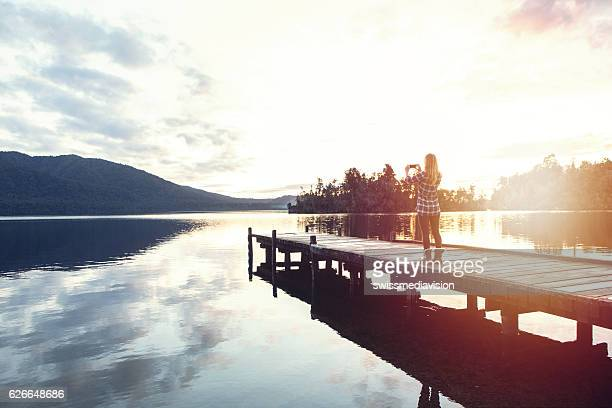Girl on pier taking photo of landscape with smartphone
