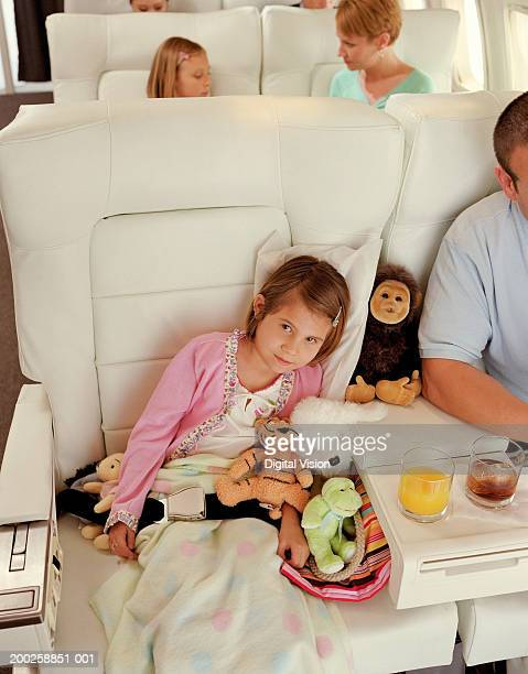 Girl (5-7) on plane with soft toys and blanket on lap, potrait