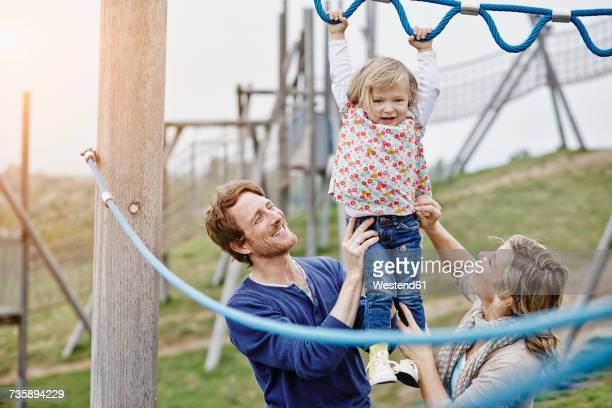 Girl on playground in climbing net supported by parents