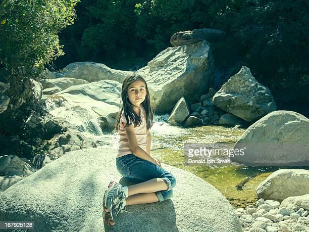 Girl on rock beside river.