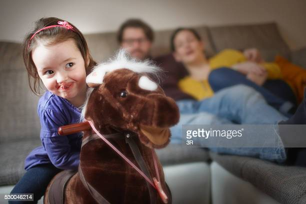Girl on rocking horse at home